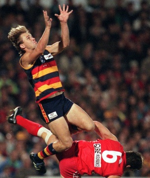 ADELAIDE CROWS VERSUS THE SYDNEY SWANS. TONY MODRA TAKES A MARK ABOVE ANDREW DUNKLEY.
